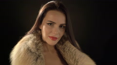 Attractive young woman posing in elegant fur jacket and sexy evening black dress - stock footage