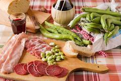 Chopping board of cold meats and broad bean - stock photo