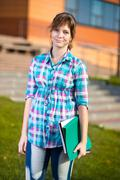 Portrait of young alluring woman holding education books. Student girl Stock Photos
