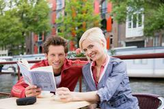 Couple with guidebook - stock photo