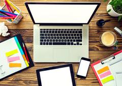 Laptop with other modern electonic devices on desk - stock photo