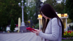 girl sitting on a bench in the park and use applications in the computer tablet - stock footage