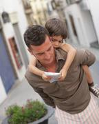 Father carrying son looking at map Stock Photos