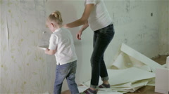 A mom and a small daughter removing old wallpaper - stock footage