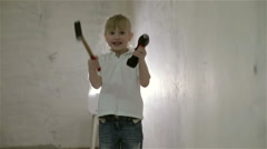 A small blond girl showing a hammer and a drill at the same time - stock footage