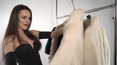 Attractive young woman chooses mink fur coat on hanger rack Stock Footage