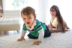 Baby first crawls, mom watches - stock photo
