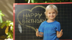 Child writing chalk on blackboard phrase: happy birthday. Stock Footage