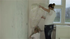 A mother and a daughter removing wallpaper, clapping and hugging - stock footage