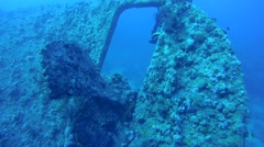 Diver swims on the undrewater scooter between the wheel and screw on the wreck Stock Footage