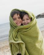 Two young children in towel on beach Stock Photos