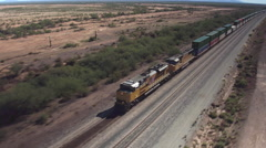 AERIAL: Long container freight train transporting goods across the country - stock footage