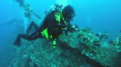 Diver with photocamera floats over the feed sunken wrecked ship SS Carnatic Stock Footage