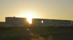 CLOSE UP: Golden sunset sun shining through freight container train wagons - stock footage