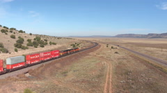 AERIAL: Long container freight train transporting goods across the country Stock Footage