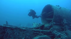 Diver inspects locomotive crashed on board the wreck SS Thistlegorm Stock Footage