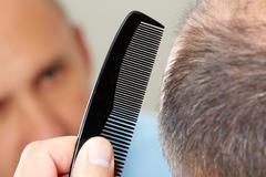 Man head with a comb. Stock Photos