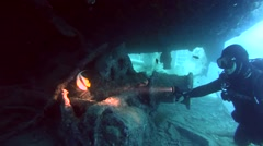 Diver looks under a railway carriage of the wreck SS Thistlegorm Stock Footage