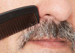 Man combing his mustache. Stock Photos