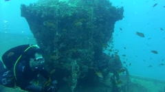 diver looks under a railway carriage of the wreck SS Thistlegorm - stock footage