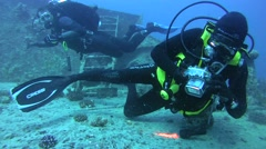 Diver photographing the red lionfish (Pterois volitans) on the wreck Stock Footage