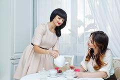 Woman pours tea girlfriend. Tea party. - stock photo