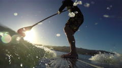 Stand up paddle board POV surfing a wave at sunrise - stock footage