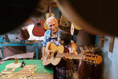 Boy Learns Play Guitar With Senior Man Grandpa - stock photo