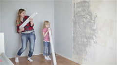 Cheerful girls are dancing and singing near the wall with rolls of wallpaper. - stock footage