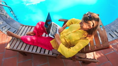 Blond Girl Sits on Folding Chair Works on Laptop by Pool Stock Footage