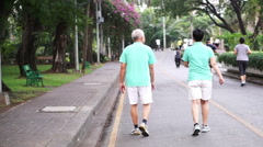 happy Asian senior couple walking exercise along the park - stock footage