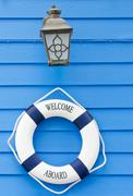 Life buoy welcome aboard sign and old lamp - stock photo