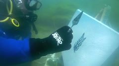 Underwater painter Yuriy Alekseev paints a picture under water Stock Footage