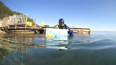 Underwater painter Yuriy Alekseev paints a picture under water Stock Footage