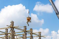 Crane working in construction on blue sky - stock photo