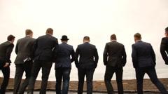 nine men in suits having fun - stock footage