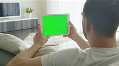 Man is Laying on Couch at Home and Watch on Tablet with Green Screen in Landscap Stock Footage