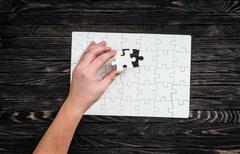 Hand completing wthite puzzle with the last piece Stock Photos