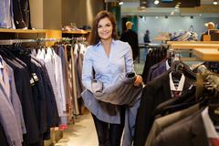 Beautiful young saleswoman helps the customer to choose a jacket in suit shop - stock photo