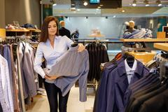 Beautiful young saleswoman helps the customer to choose a jacket in suit shop Stock Photos