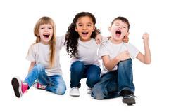 Three funny trendy children laugh sitting on the floor Stock Photos