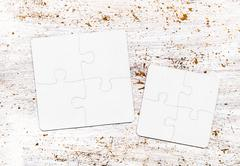 Different size pieces of white puzzle on a table Stock Photos