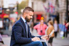 Hipster manager working on laptop on Piccadilly Circus, London - stock photo