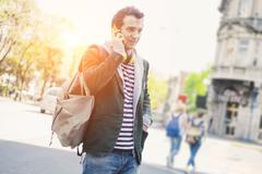 urban man casual clothing in the city calling under the sun with sun flare ar - stock photo