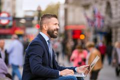 Hipster manager working on laptop on sunny Piccadilly Circus, Lo - stock photo