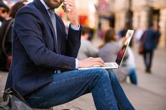 Manager with laptop and smart phone, Piccadilly Circus, London - stock photo