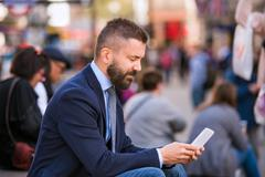 Hipster manager with mart phone, Piccadilly Circus, London - stock photo