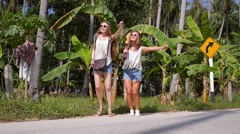 Boho Hippy Young Girls Hitchhiking on Road Travelling - stock footage