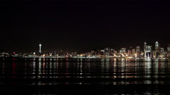 Slow pan across Seattle skyline  night time  with waterfront in foreground Stock Footage
