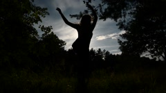 Dancing girl silhouette against the sky Stock Footage
